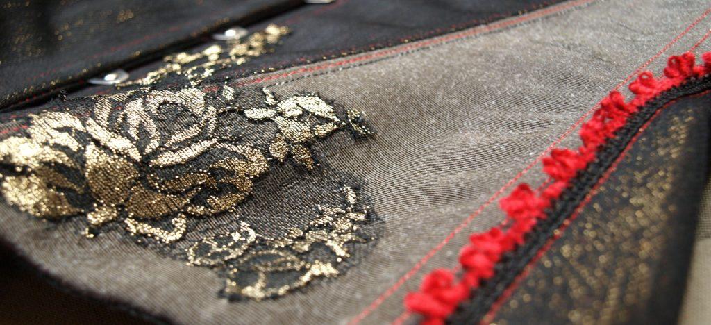 Dentelle or incrustée à la main sur un corset en jean